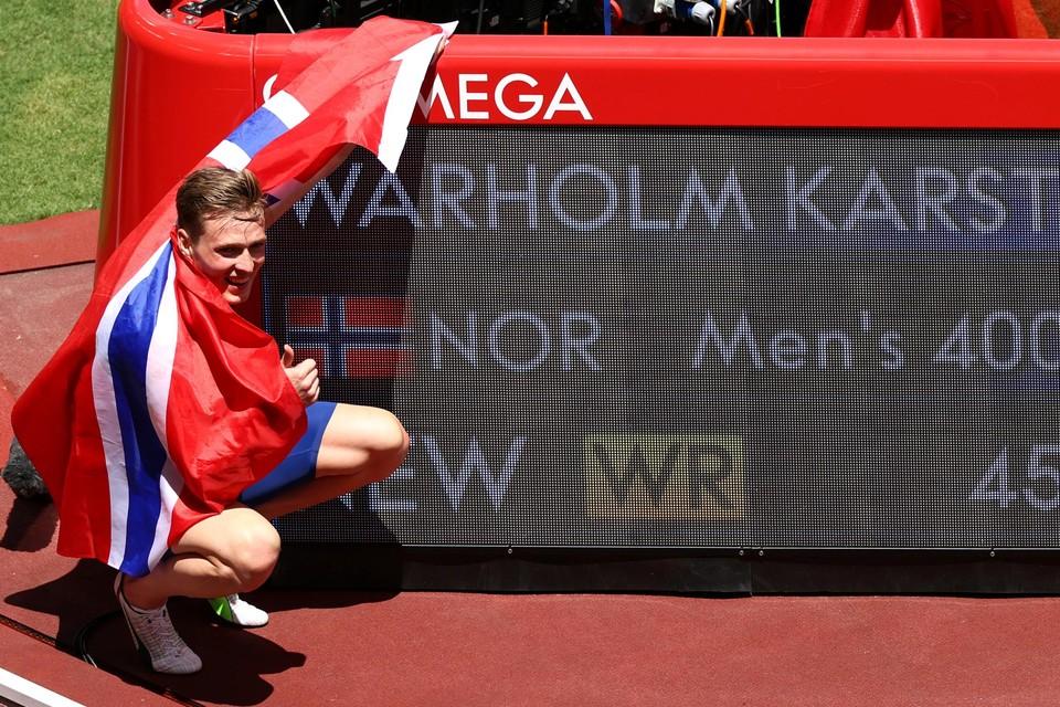 Het klassieke beeld. Atleet hult zich in vlag en poseert glimlachend voor een nieuwe recordtijd. Karsten Warholm voert na zijn 400m horden het ritueel uit.
