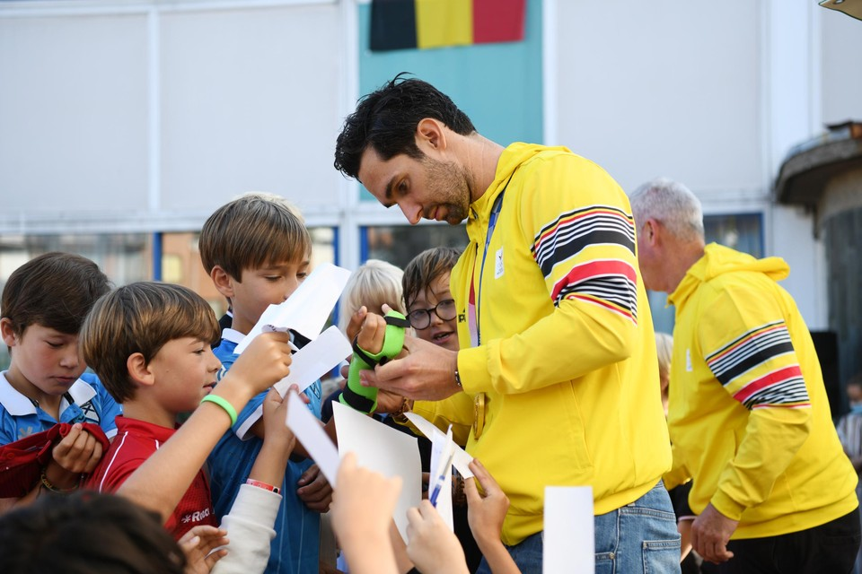 De hockeyspeler en -coach delen handtekeningen uit.