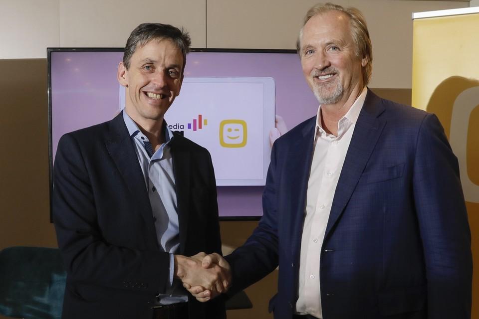 Kris Vervaet (links), CEO van DPG Media, en John Porter van Telenet slaan de handen in elkaar.