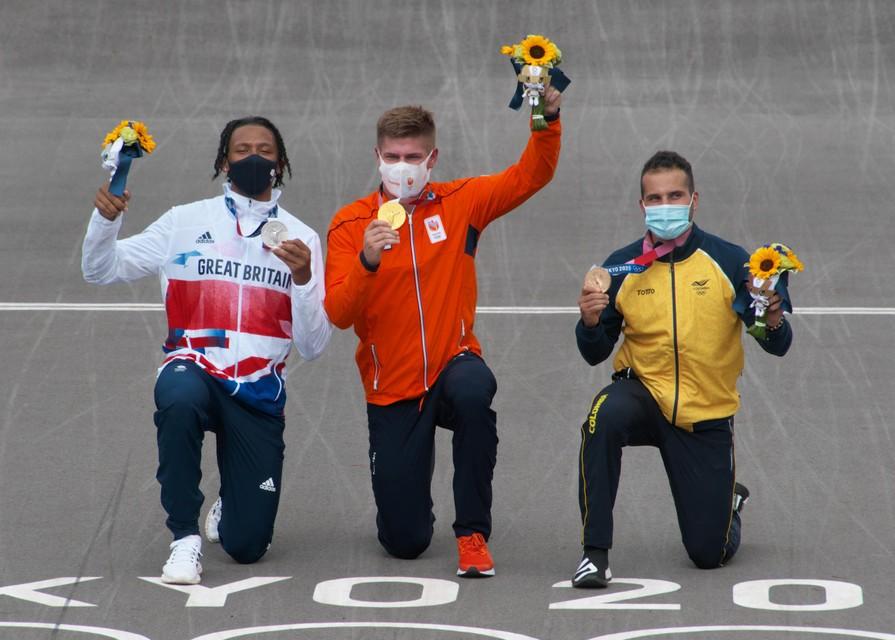 Heel bewust steunde Niek Kimmann (midden) op zijn rechterknie toen hij zijn gouden medaille aan de pers showde. In zijn andere knieschijf zit er een scheur.