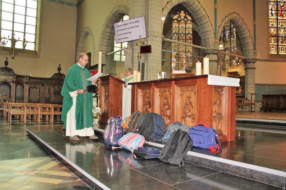 Priester Danny Adams zegent de schooltassen met wijwater.