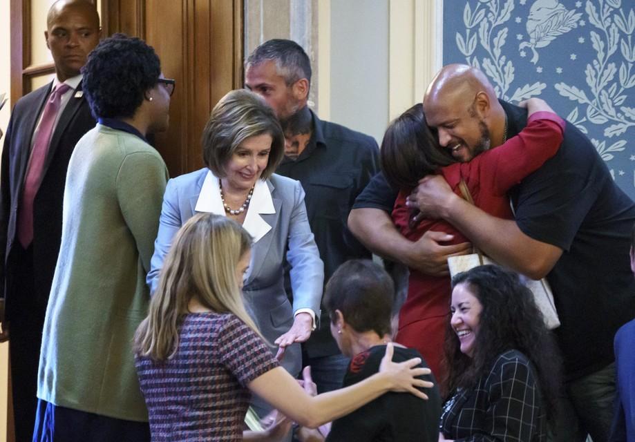 Nancy Pelosi (centraal) tussen verheugde nabestaanden en politieagenten.