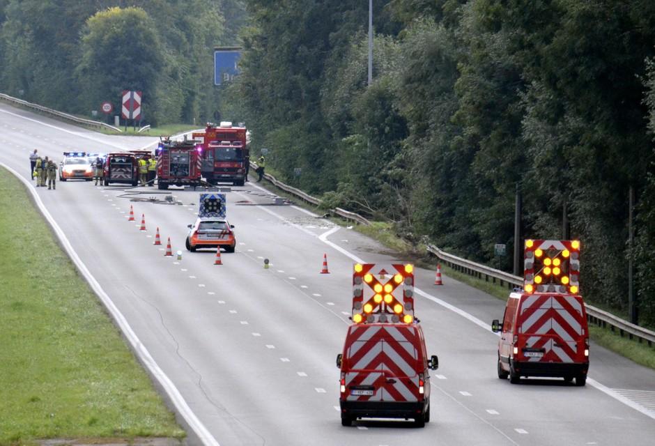 De gekantelde tankwagen ligt in het weiland naast de snelweg.