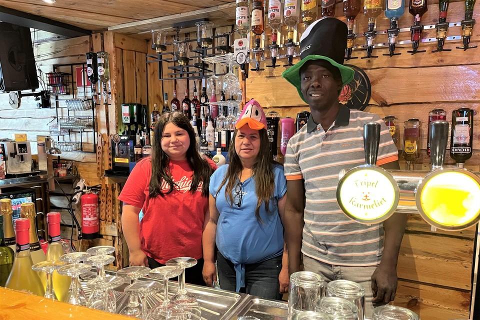 """Thailia, Chantal en Lamine achter de toog, met tientallen flessen in de achtergrond. """"We bieden elke week meer dan 100 verschillende shots aan."""""""