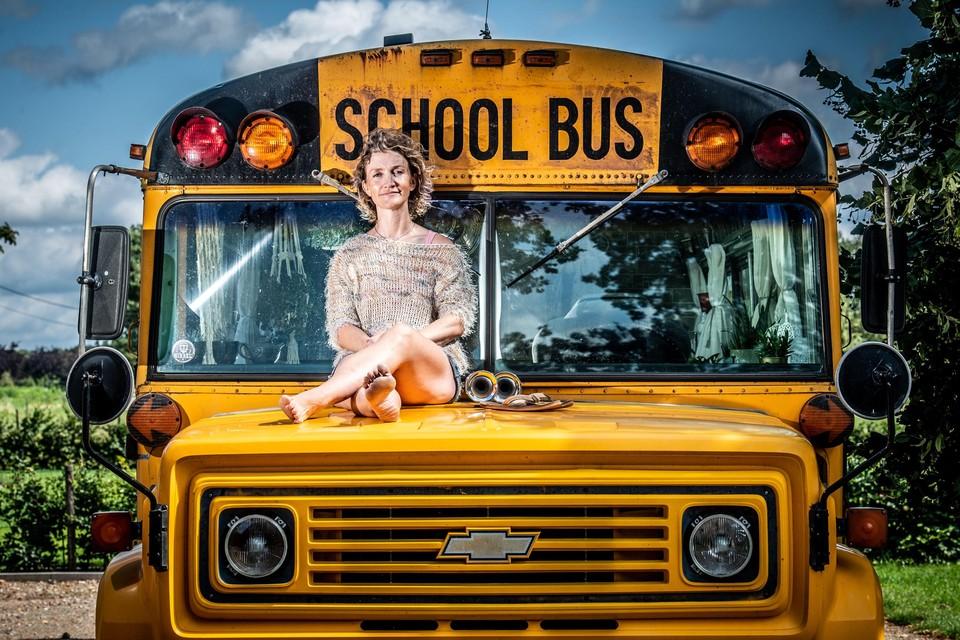 Christel Ramaekers op de motorkap van Ophelia, de oude Amerikaanse schoolbus waarin ze nu woont.