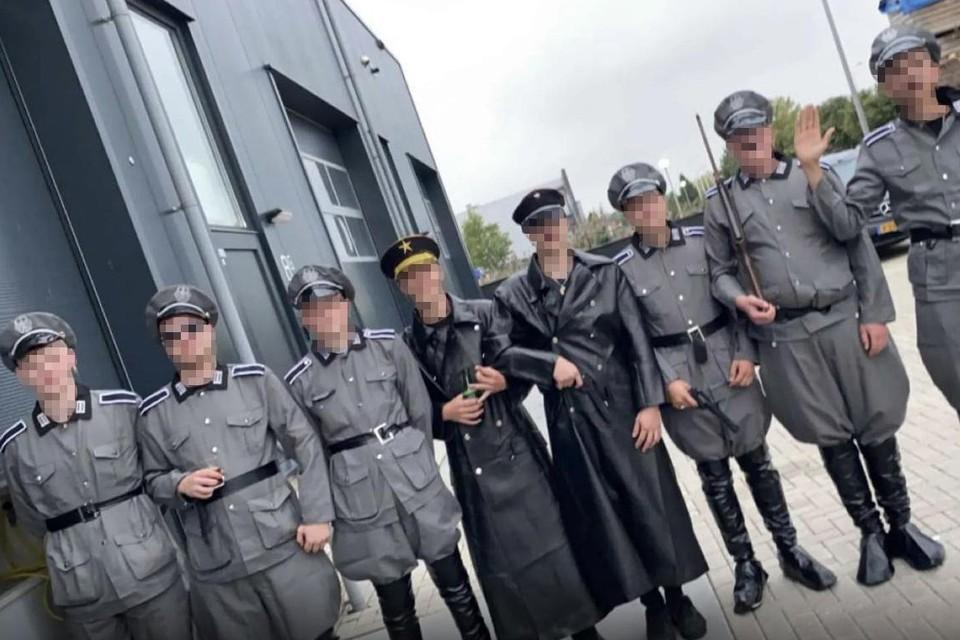 De bende, sommigen met Hitlersnorretje, anderen verkleed als Gestapo, op stap in Urk.
