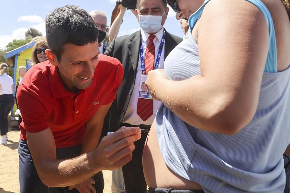 Novak Djokovic zet na zijn zege op de Australian Open zijn handtekening op de zwangere buik van een fan.