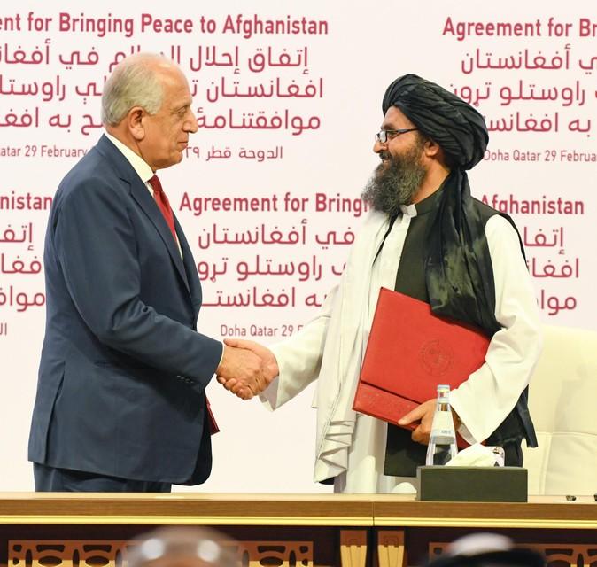 Amerikaans gezant Zalmay Khalilzad en medeoprichter van de taliban Abdul Ghani Baradar bij het ondertekenen van het eerdere akkoord in 2020.