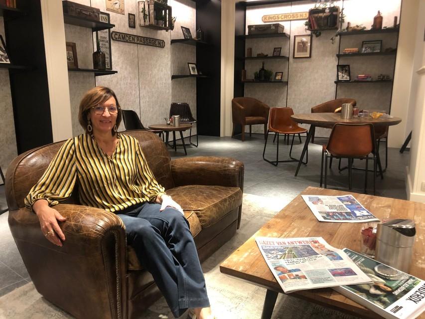 Inge Van Peer zit in de koffiehoek van de kledingzaak in Poederlee. Klanten kunnen daar even de krant lezen en genieten van een kop koffie.