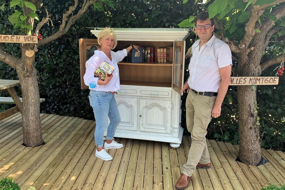 Schepenen Lili Stevens en Luc Van Houtven vullen de boekenruilkast.
