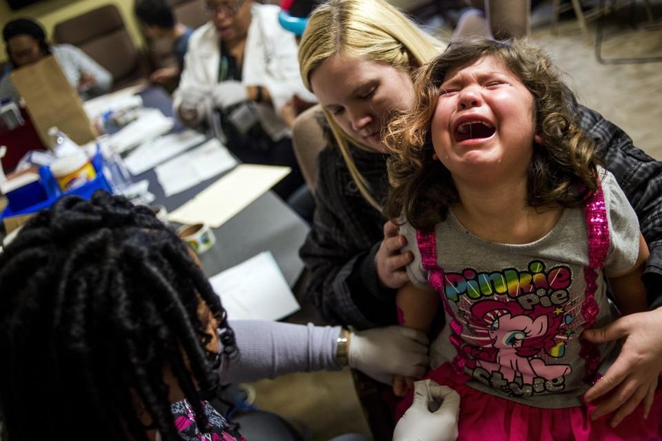 Een meisje wordt getest op lood in haar bloed.
