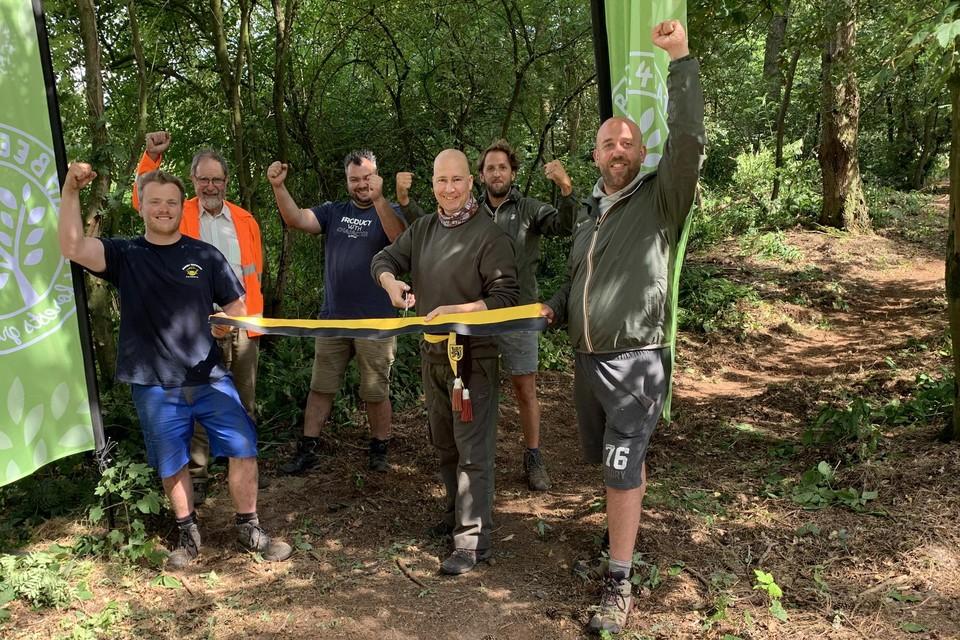 De Geelse milieuschepen Bart Julliams (N-VA) knipt officieel het lintje door van het bos dat Pieter Vanhoof (links), Kevin Vleminx (tweede van rechts) en Jeroen De Muynck (rechts) van Beer 4 Nature samen met vrijwilligers van De Bosgroep Zuiderkempen toegankelijk maakten.