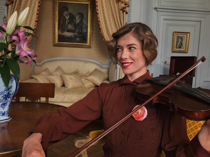 Een actrice speelt koningin Elisabeth op haar viool na.