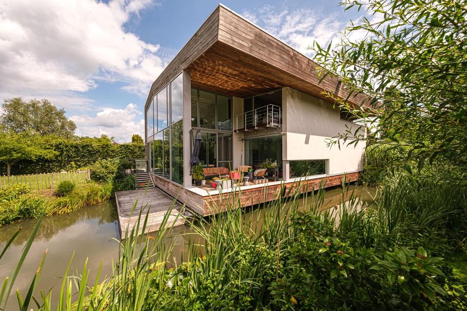 Deze unieke villa in Herenthout, gebouwd in 2011 op betonnen palen boven een vijver, staat te koop voor 1.215.000 euro.