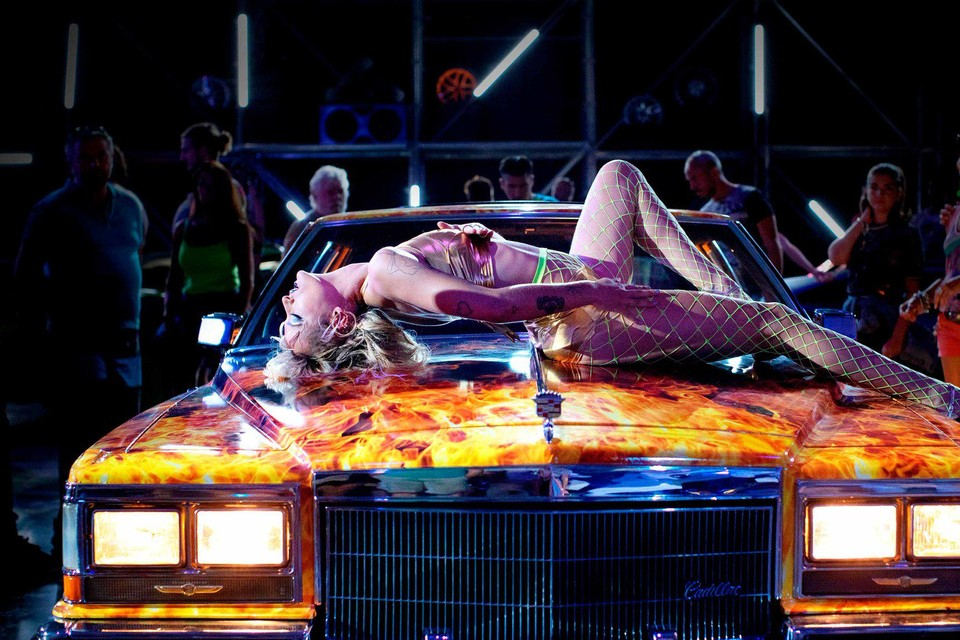 Alexia kronkelt als een hostess op een autosalon over een glimmende slee.