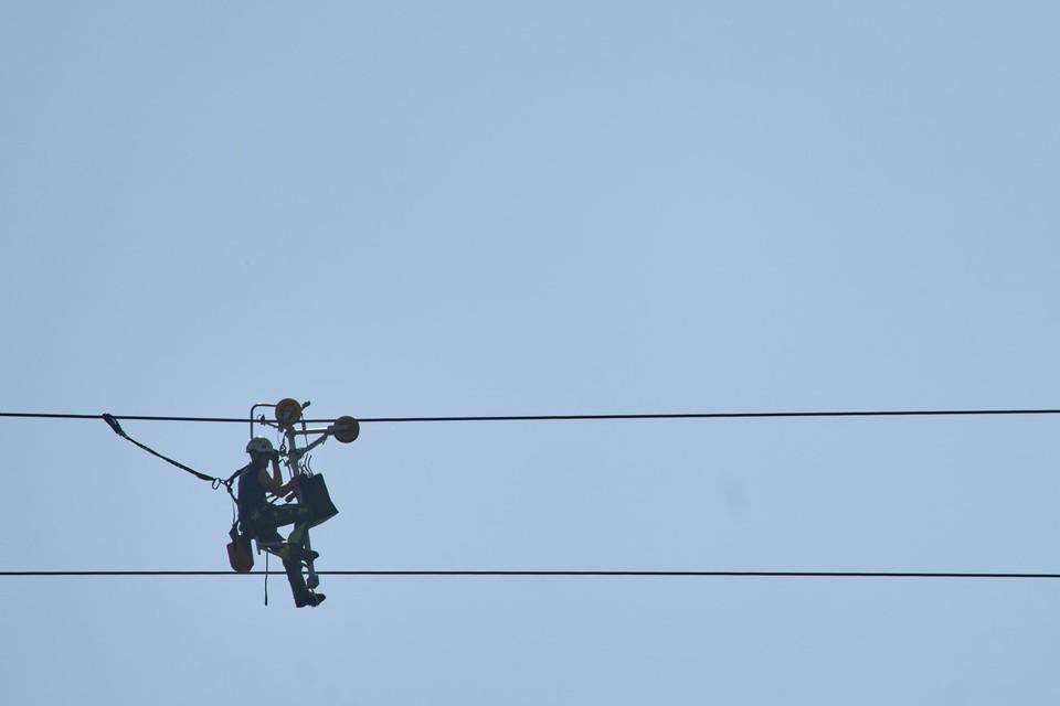 Een arbeider fietst over de draden